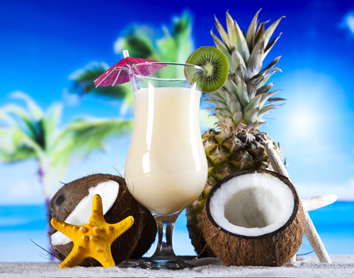 white drink with an umbrella next to a starfish and a coconut